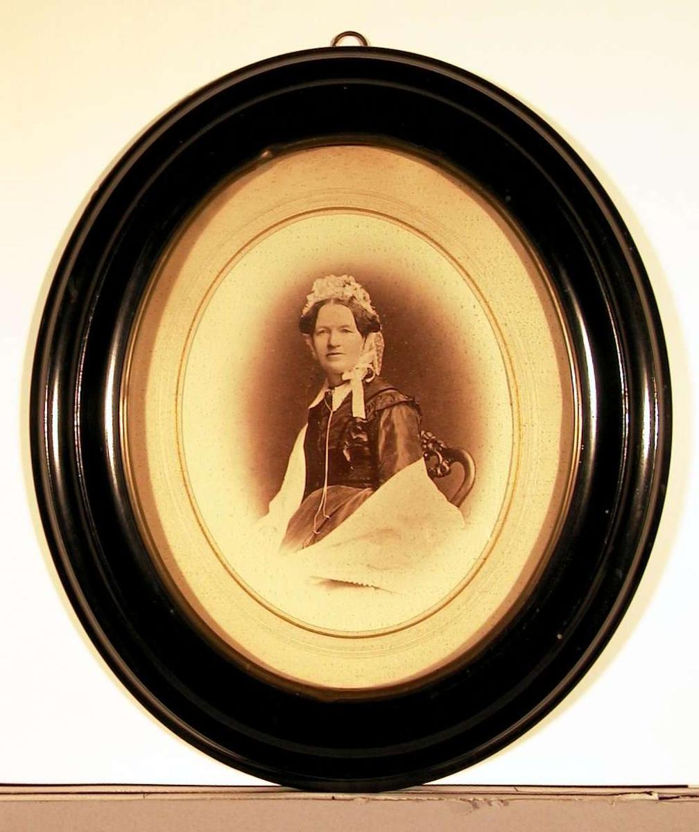 Portrettfotografi av voksen dame sittende med oppsatt frisyre, kyse og sjal. Hun ser direkte på betrakteren.