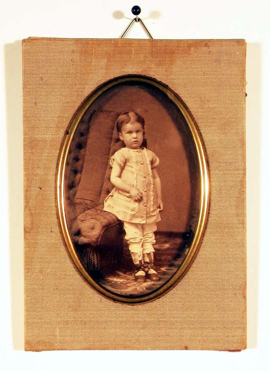 Fotografi av en liten pike stående ved polstret lenestol; hun er kledd i lys forkleskjole og hvite mammelukker med rutete strømper og åpne sko med silkebånd og sløyfer. Hun er direkte på betrakteren.