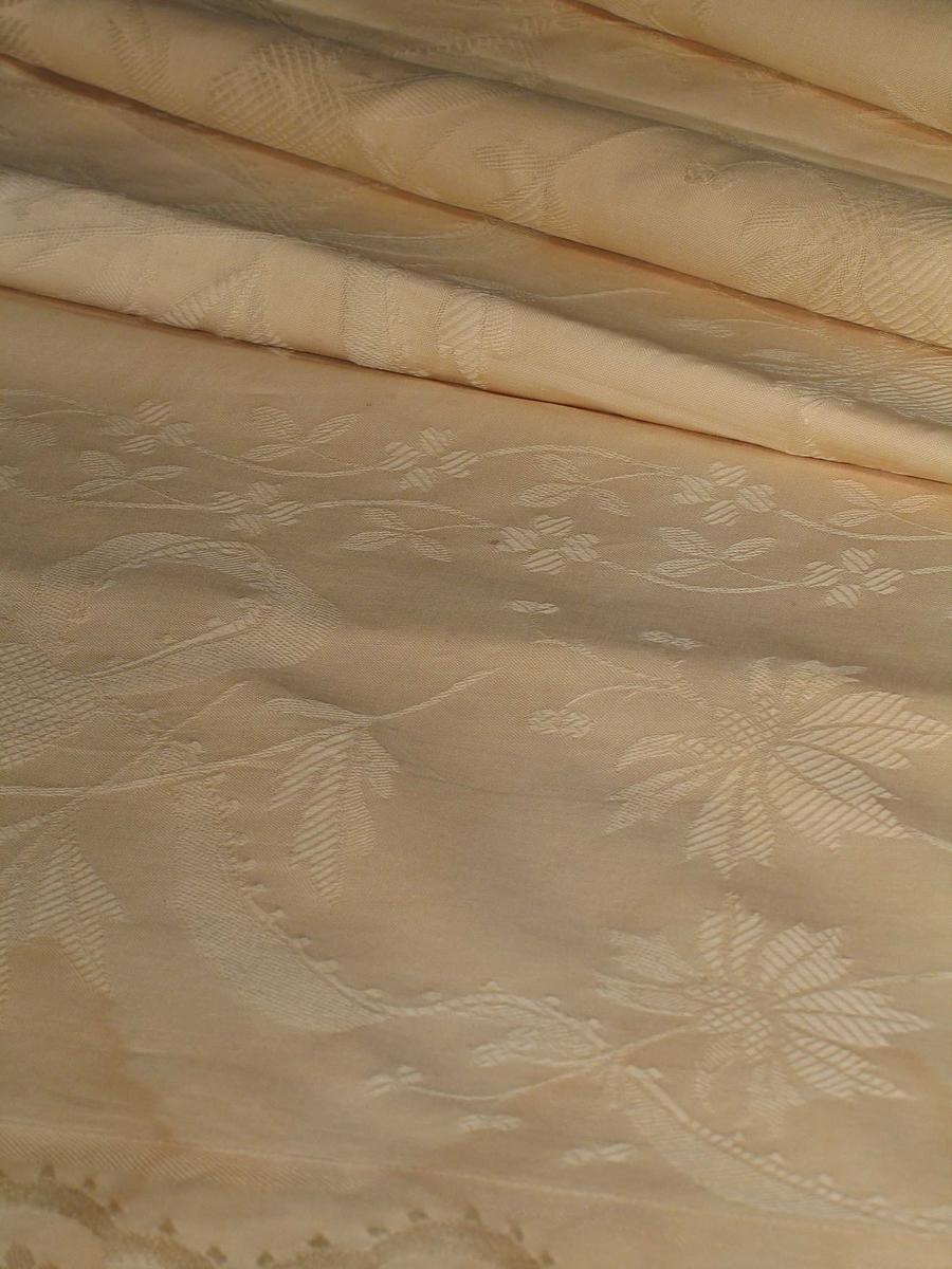 Gardin i ecrufarget jacquardvevet bomullstøy. Mønster: skiftevis brede og smale vertikale blomsterranker med sløyfebånd.
