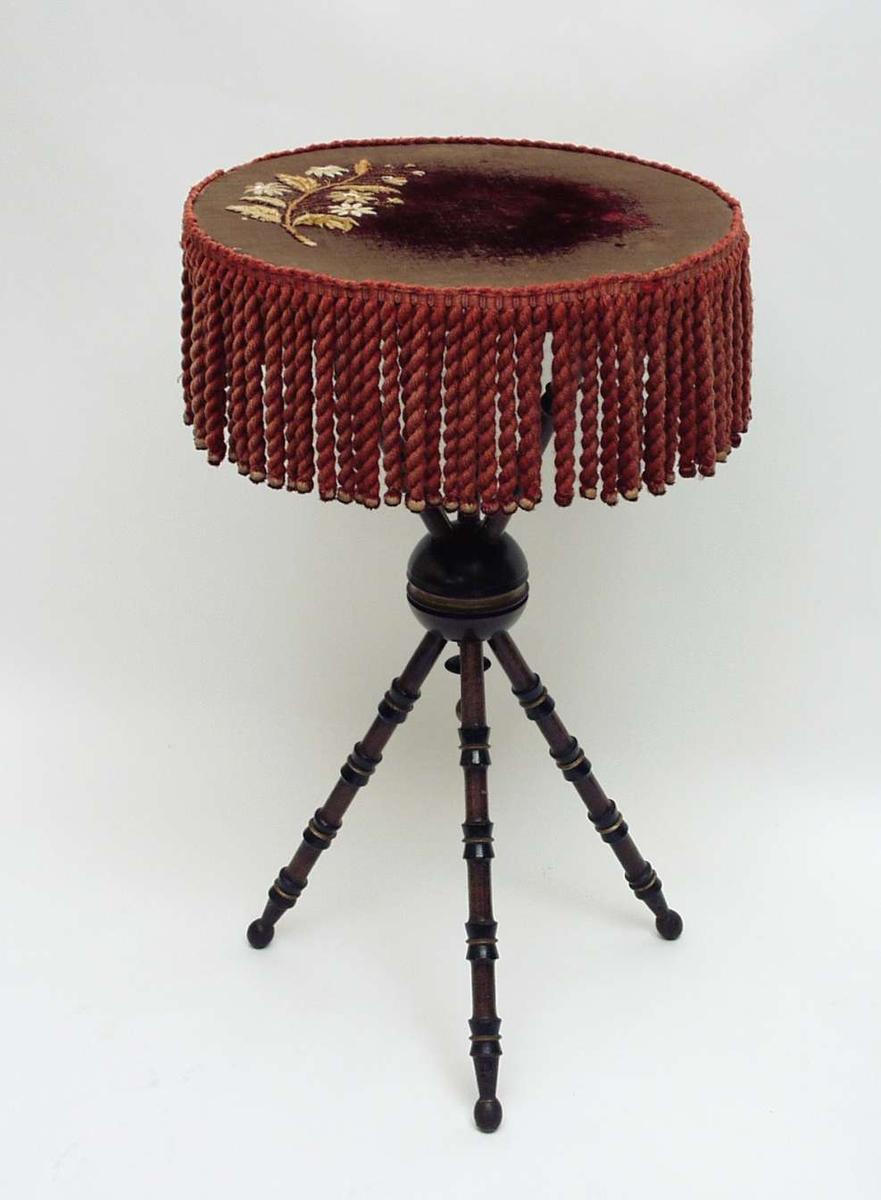 Rundt lite bord med tre dreide ben holdt sammen av en kule. Bordplaten er trukket med burgunder tekstil. Det har frynser rundt kanten med trekuler nederst. Brodert blomstermotiv i gult. Understellet er beiset svart med striper i gull.