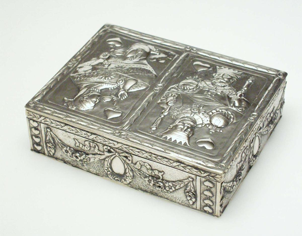 Skrin i sølv. På lokket er det bladmønster langs kanten, dame og konge. På sidene er det en krans med sløyfe, alt i relieff. Skrinet inneholder to kortstokker.