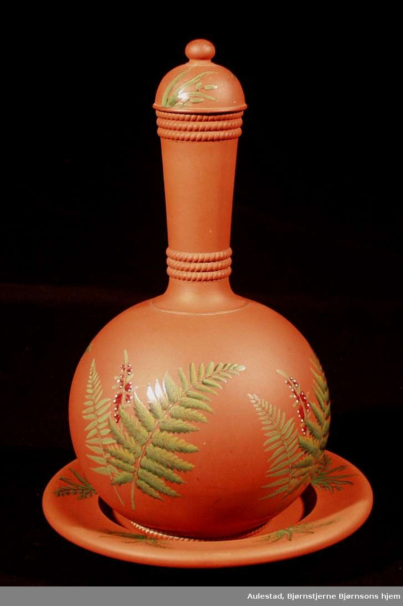 Karaffel bestående av underskål og vannbeholder med lokk. Vannbeholder i ballongform med lang hals. Dekorert med grønne bregneblader, 3 skraverte ringer rundt halsen og nede og en skravert ring ved fotstykket.