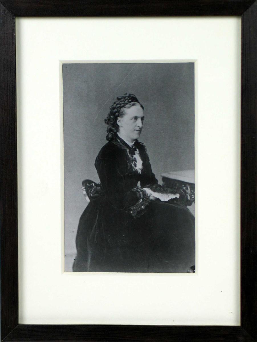 Karoline Bjørnson fotografert sittende i atelier. Hun bærer en mørk fløyelskjole med blonde på ermer og halsutringing. Hvit bluse og svart korsformet halssmykke.
