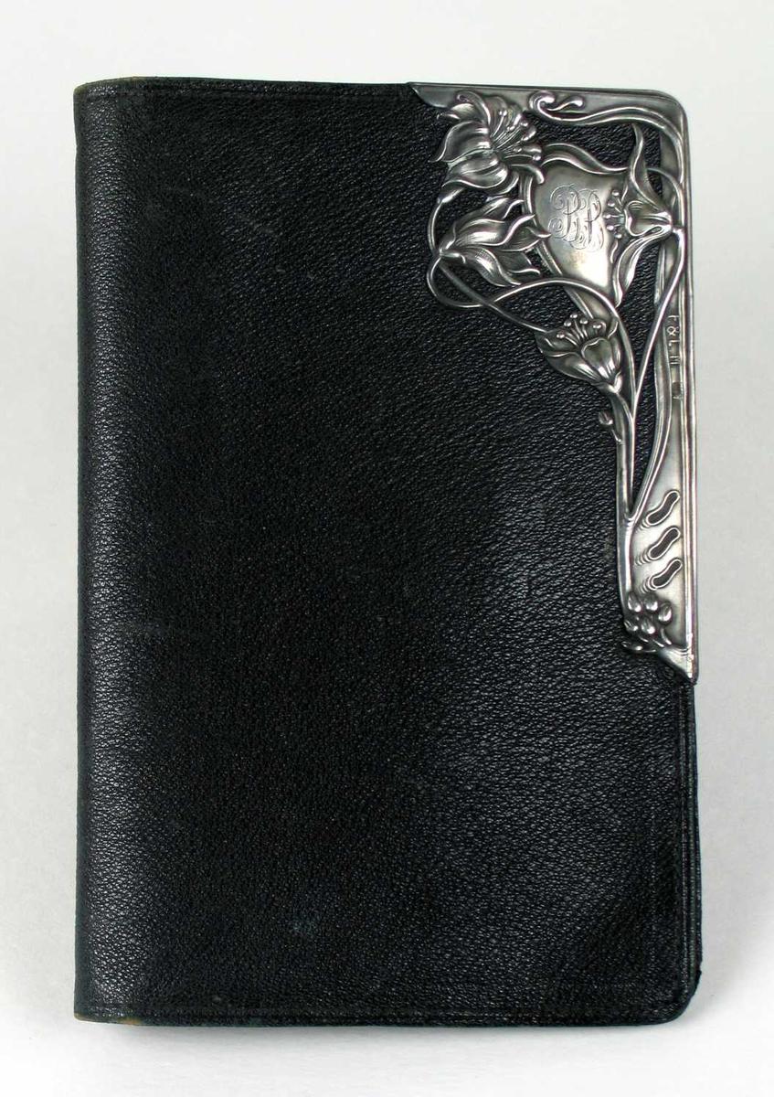 Seddelbok i svart skinn. I høyre hjørnet et sølvornament i jugendstil med monogrammet BB.