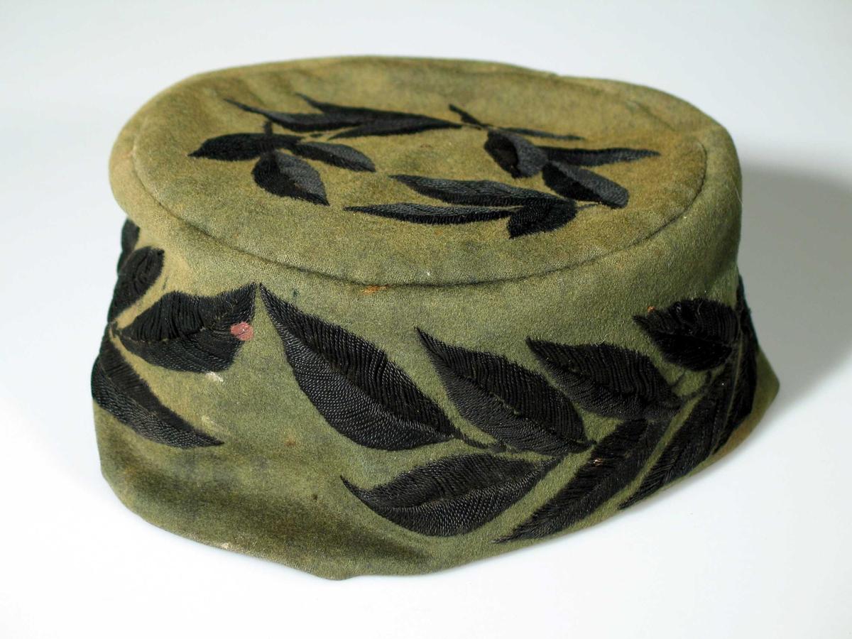 Grønn kalott i tynn filt med svart blad brodert på toppen og rundt kanten. Lua er sydd av to stykker grønt tøy. Toppen er rund og sidestykket har søm midt bak. Broderiet i plattsøm er formet som laurbærblad. Det svarte silkefôret er nesten morknet vekk.