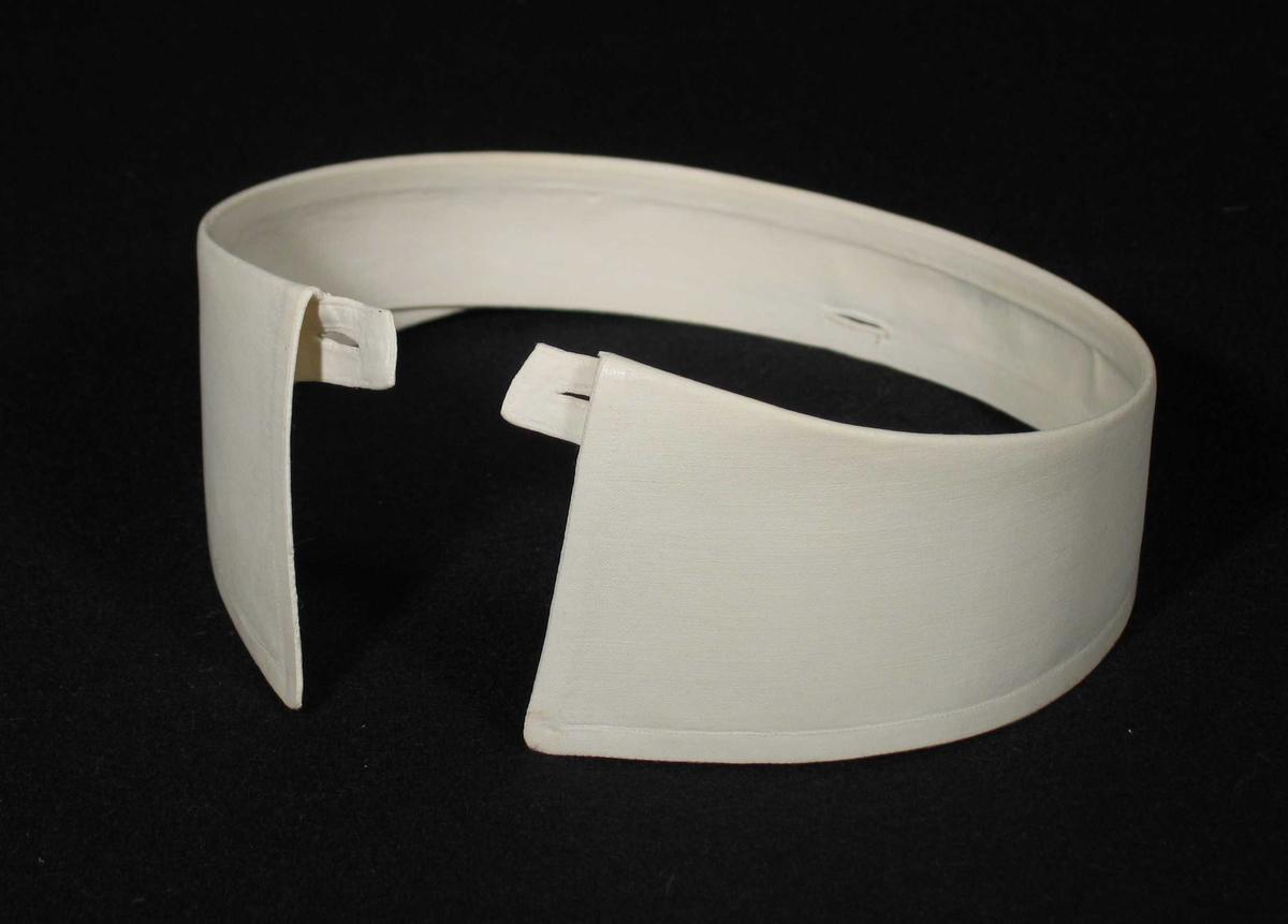 Stivet hvit snipp i toskaft bomullsstoff. Et knapphull på hver side og et midt bak.