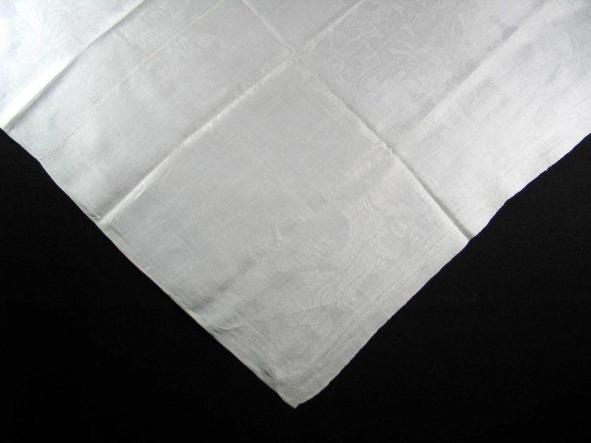 Hvit linduk med monogram. Duken er vevd i jacquardteknikk. Duken har jarer i langsgående sider og 3 mm brede håndsydde falder på tvers. Mønsteret utgjør et avsluttet hele. Rettlinjet 3,6 cm bord av enkle valknuter med hjørneløsning langs ytterkanter. Ca 30 cm bred bord av bladverk i sirkler, fem sirkler på bredden, seks sirkler på lengden medregnet hjørnesirklene. Hjørnemotiv: to asymmetrisk, motstående fugler (fasaner?), dernest en og en fugl (hane, fasan) Midtpartiet er speilvendt symmetrisk, men har et stadig forandret mønster i høyden. Ved bunnen to fasaner vendt fra hverandre. Ellers blomsterranker og bladverk. Brodert monogram, B på vranga i det ene hjørnet.  (Dette er et usedvanlig fint maskinvevd produkt, både materialmessig, fintstillthet og mønstermessig. Holland?  8/5-87 R.B.R.)