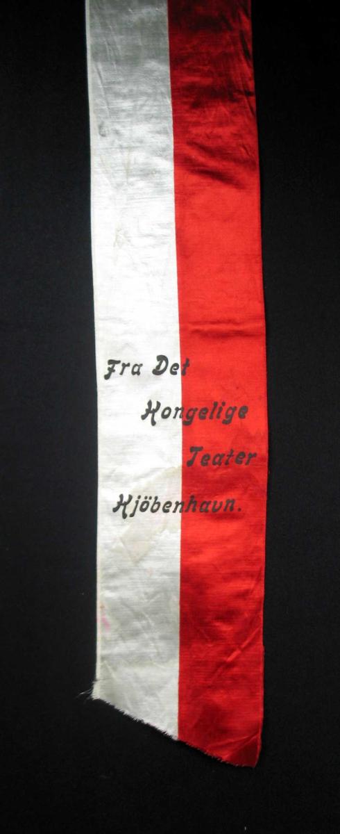 Begravelsessløyfe i hvit og rød silke med svart tekst.