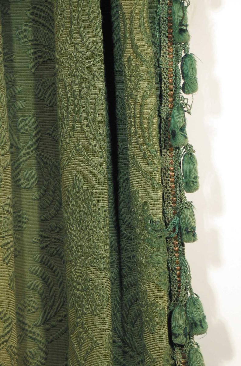 To mørk grønne portierer og kappe med dusker og innvevd kobbertråd. Jacquardvevd med flotteringer på ripsbunn. Mønstring ved flottering av mercerisert bomull. Motiv: Palmett i oval form, omg. av bladverk; stilisert. Mønsterets rapport er høyden 37 cm, i bredden 20 cm. Vevde kantbånd med dusk/pompong pr. 5 cm. Portièrer kantet med bånd på én langside og nederst på side-portièrer og nederst på kappen. Hengt opp foran døråpningen med en lengde på hver side, med kappe mellom. Portierene er festet til trefjøl over verandadør med knappenåler