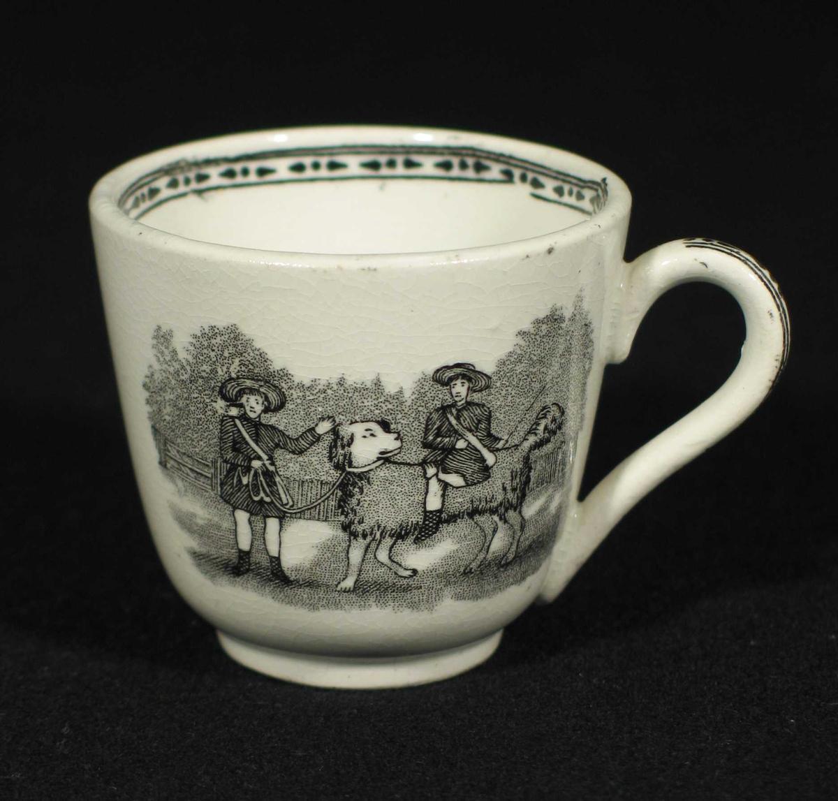 Hvit kopp med svart bord innvending og på hanken. To forskjellige motiv på sidene.