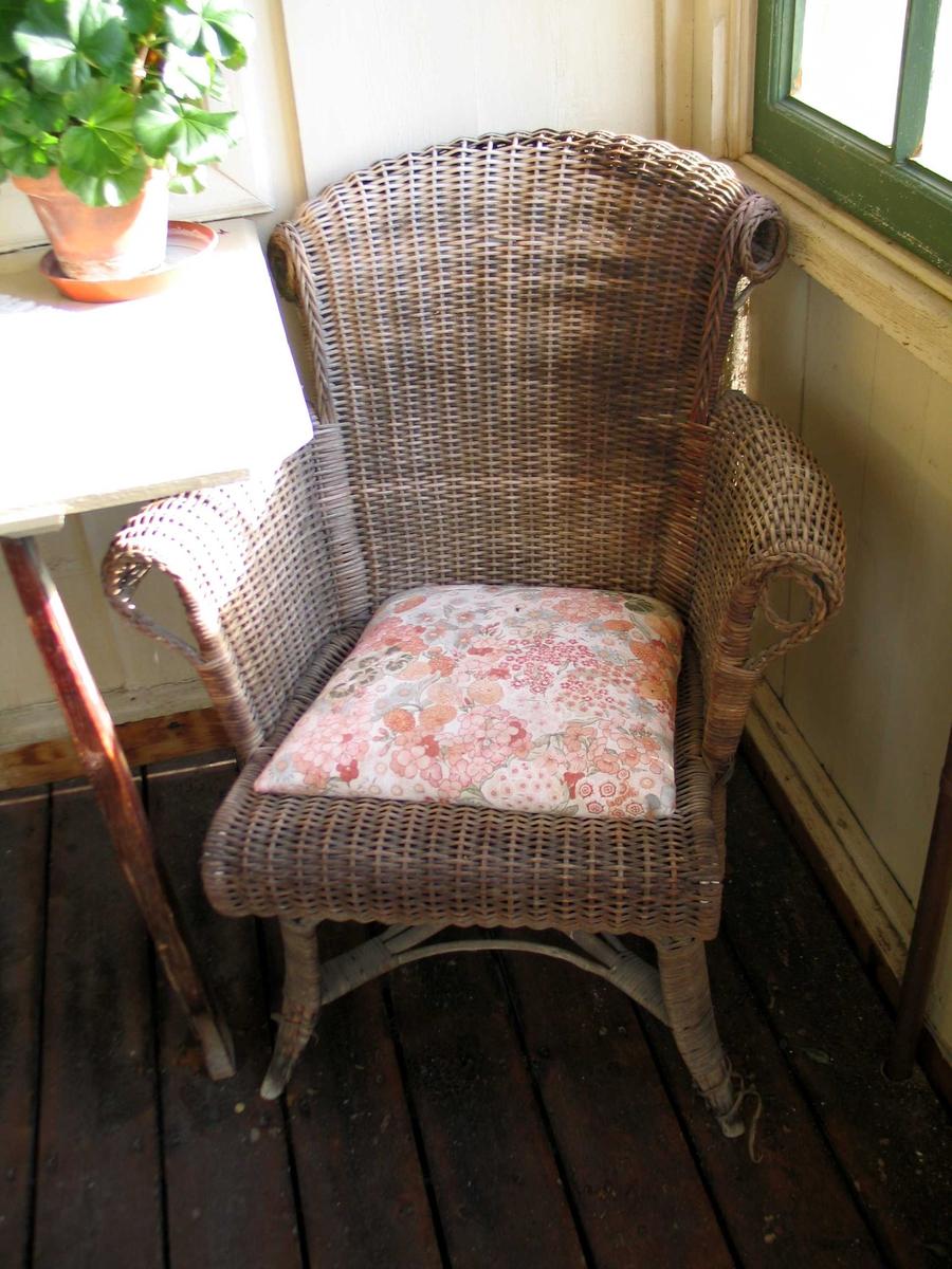 Kurvstol med armlener, buet rygg og flettet dekor langs kantene.