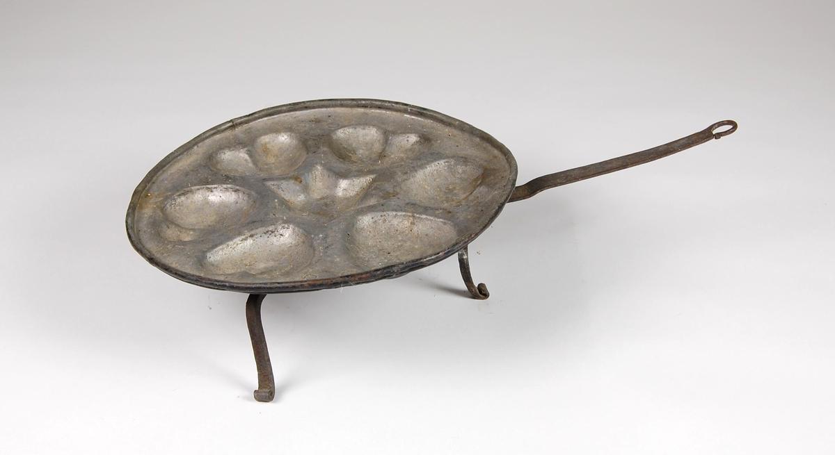 Munkepanne av kobber med fortinnet bunn og seks hjerter med stjerne i midten. Panna har tre bein og håndtak.