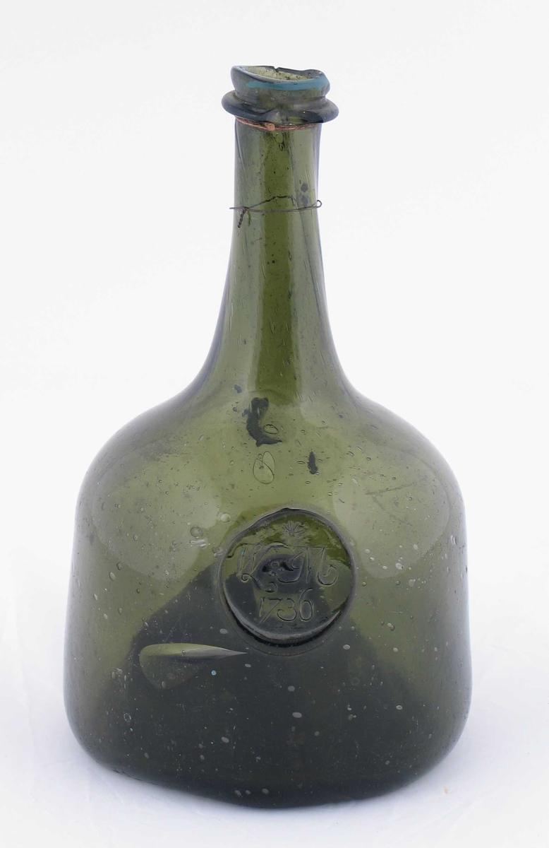 Grønn flaske med stempel på utsiden. Den første initialen i stempelet, W, er usikker.