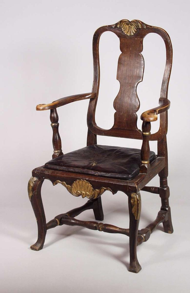 Stolen er av gran og løvtre, malt brun med gulldekor på de utskjærte områdene. Setet er stoppet lærtrekk. Armlenstøtte og midt/sidespross er dreid.