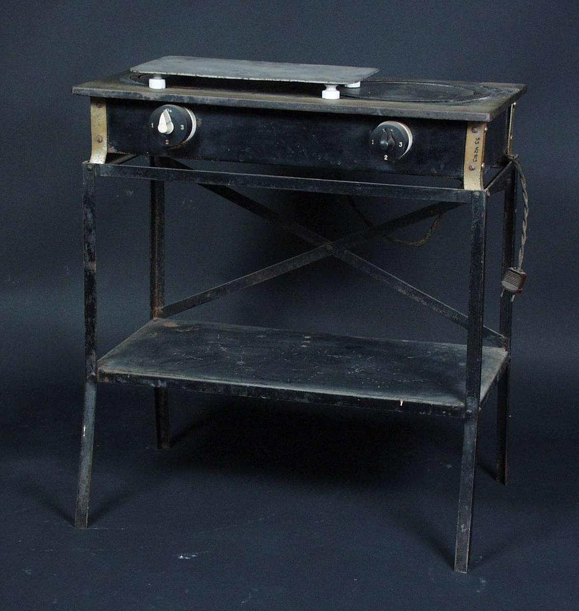 En liten komfyr med bare to kokeplater og en hylle under platene. Komfyren har fire ben.