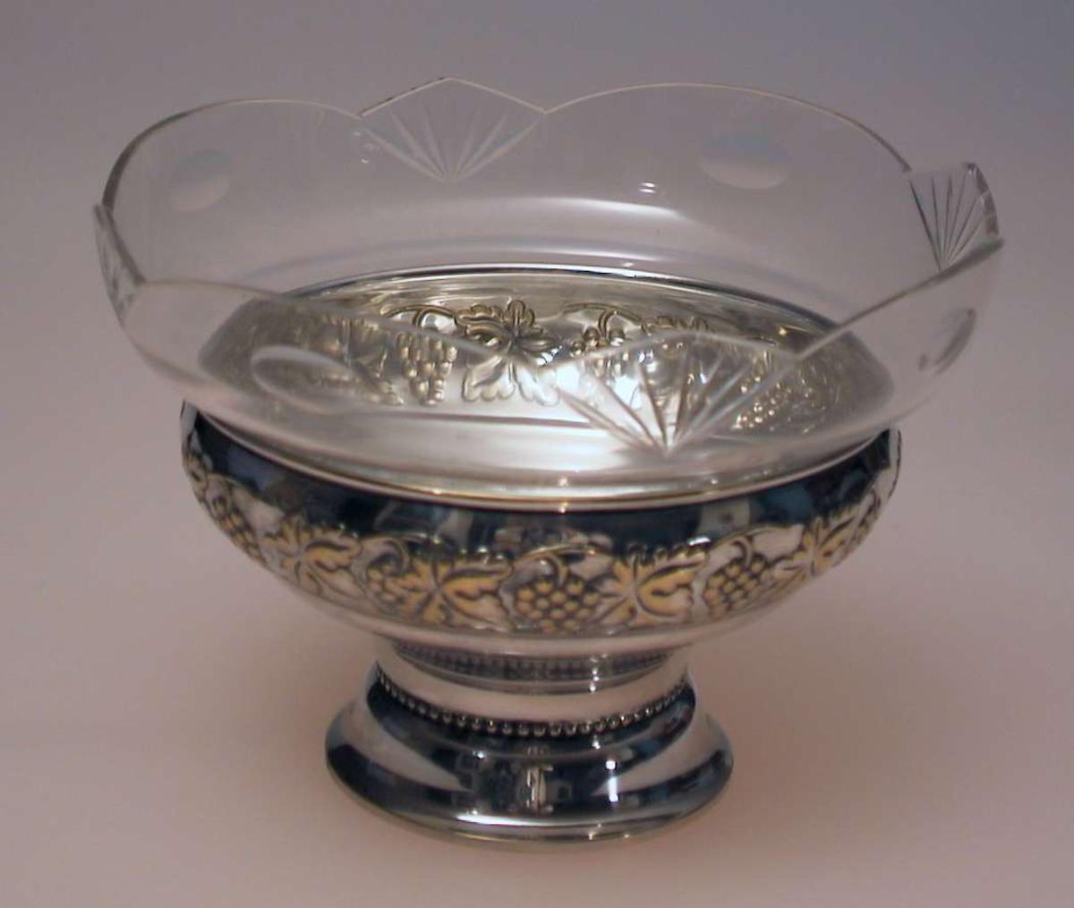 Bolle i sølvplett med glasskål. Bollen er dekorert med drueklaser. Skålen har bølget kant og vifteformet dekor slipt inn.