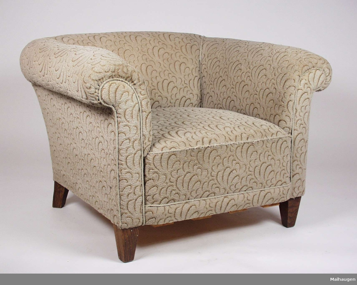 Stolen har ramme av tre, og er stoppet med mønstret brunt og beige tekstil. Stolen har påsatt nyere treplanker under setet.