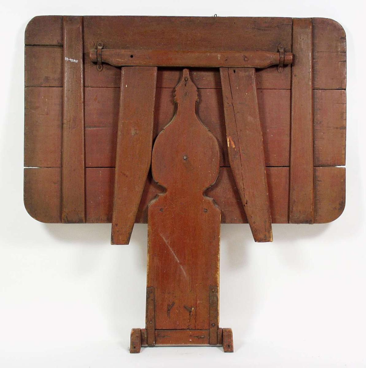 Firkantet klaffebord av furu som festes med fire spiker inntil en vegg. Bordet er malt i rødbrun farge. Kan slås opp. Planken under bordplaten har utskjæringer og er festet med jernspiker.