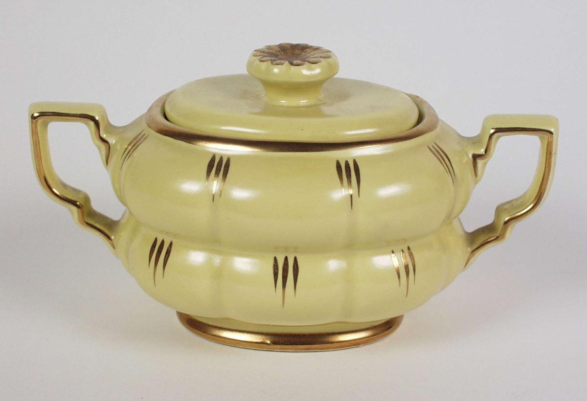 Gul sukkerkopp med lokk i porselen med gullkant og enkel strekdekor. Koppen har to hanker, og på lokket er knotten rosettformet.