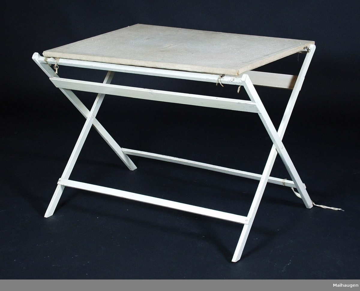 Et hvitt stellebord i gran.  Stellebordet har ikke badekar. Det festet til bena med hengekrok som er på stelleplaten. Stelleplaten er av lerret. Stellebordet er sammenleggbart.