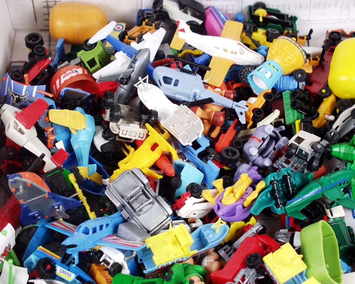 Pappeske fylt med ulike figurer laget av plast: fly, biler, helikopter, båt og dyr på hjul.