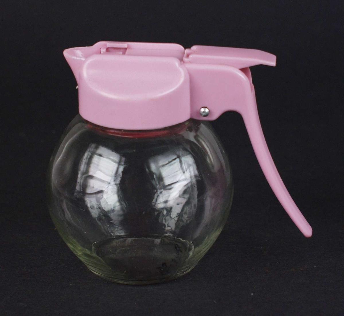 Liten serveringsmugge i glass med rosa lokk i plast.