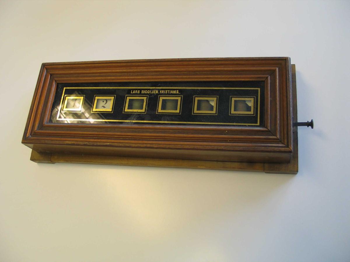 Signaltablå med seks felt. Beregnet for tilkalling av hushjelp i private hjem. Brukes sammen med en ringeklokke. Sinaltablået er som regel plassert på kjøkkenet og angir hvilket rom det ringes fra. Tablået er utstyrt med seks elektromagneter som senker hvert sitt flagg avhengig av hvilket rom det ringes fra. Elektronikken er skjult inni et skap av mahogny, og flaggene er synlig gjennom et glassfelt. Glassfeltet er belagt med bladgull og sort maling som danner en omramming omkring de seks separate feltene. Flaggene heves tilbake ved å trykke inn et stag på siden av tablået.