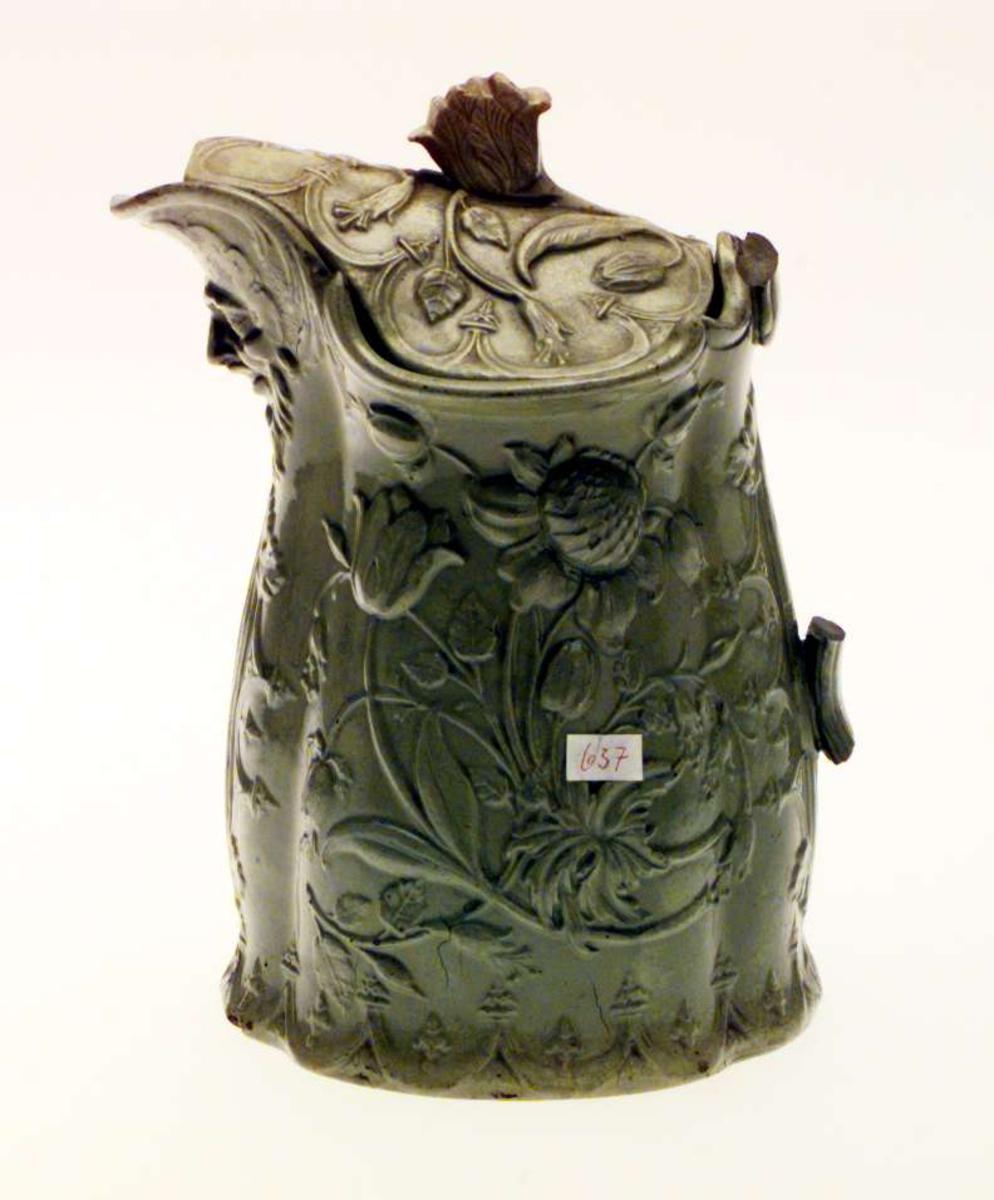 Mugge med lokk i keramikk. Hanken er slått av og det det er skår i nebbet og i lokket. Muggen har akantusdekor og border i relieff. Muggen er utstyrt med en maske under nebbet (bartmann). Muggen er grønn.