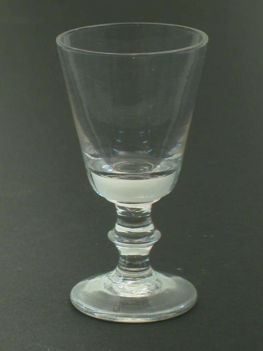 Brennevinsglass med skive på stetten. Klokken er konisk.