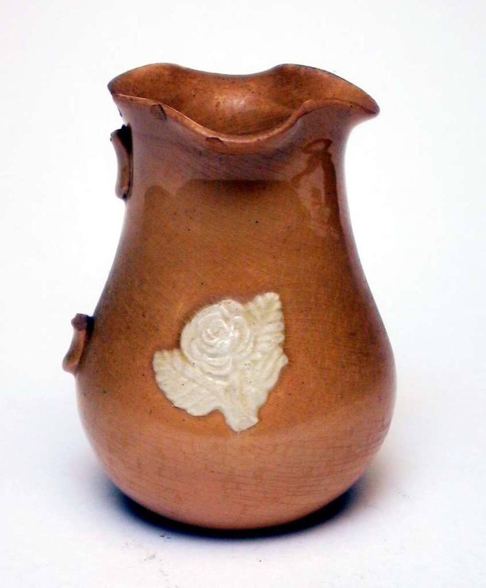 Mugge av gul keramikk med påsatt blomsterdekor. Dekoren er elfenbenshvit. Hanken mangler. Det er slått skår av munningsranden. Kannen har ingen produksjonsmerker.
