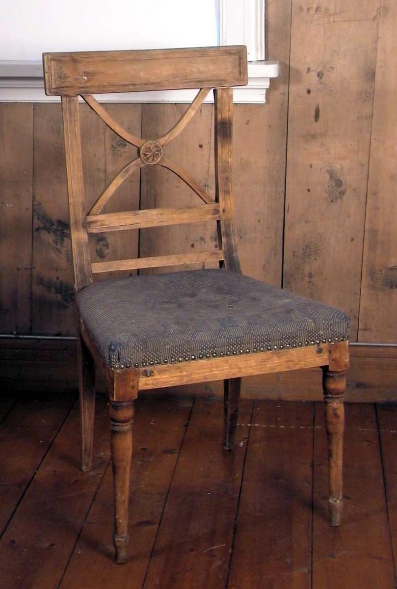 Trehvit spisestuestol med Andreaskors i ryggen og med stoppet sete. Stoffet i setet er blått og beige i et rutemønster. Trekket er flekkete og hullet. Treverket i ryggstøet er sprukket og løst.