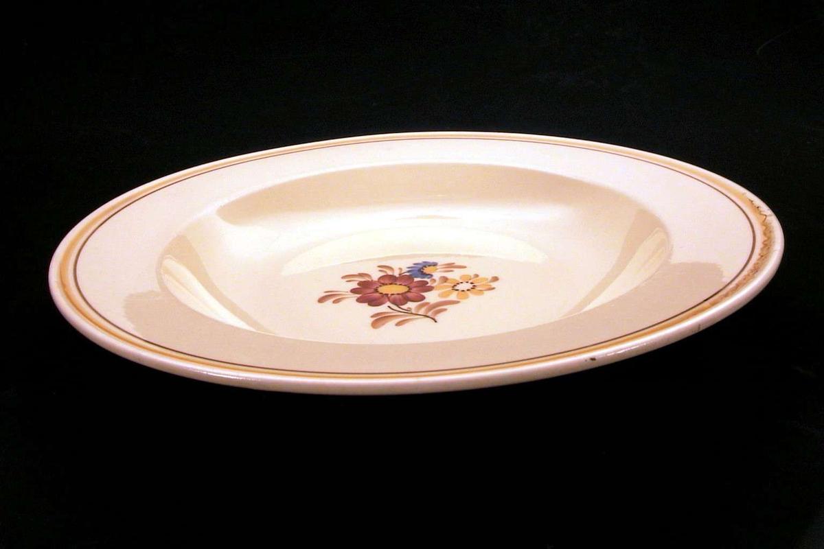 Gul tallerken med blomsterdekor på midten og med en oker og en brun linje langs kanten.
