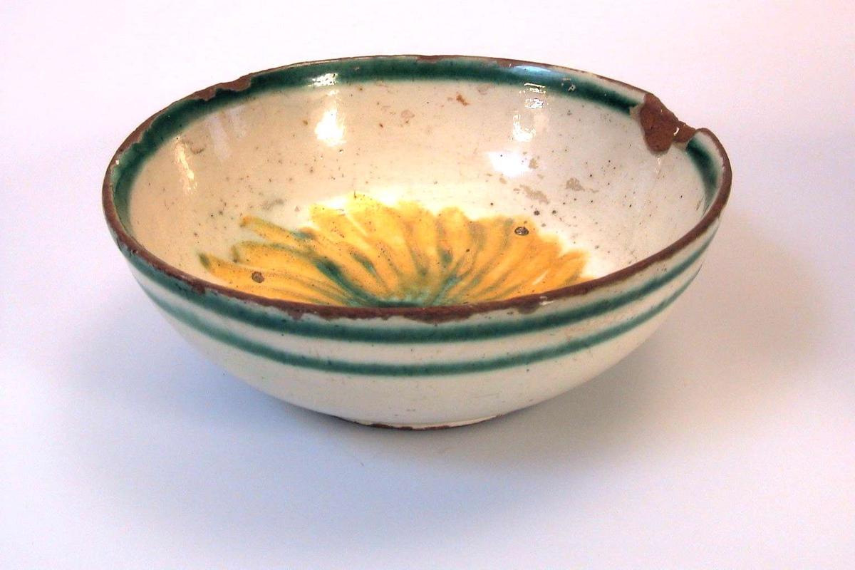 Dessertbolle med kremfarget glasur med dekor i gult og grønt, og en grønn ring langs kanten. Brukskunst.
