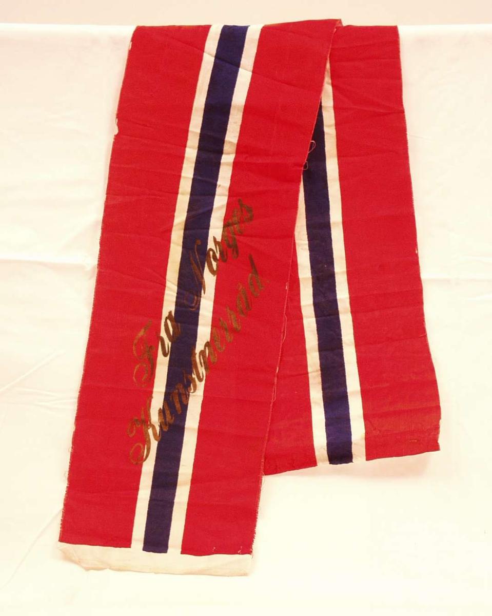 Bånd i rød, hvit og blå silke; flaggremse. Båndet er i to deler. På det ene står det i forgylte bokstaver: Fra Norges Kunstnerråd.
