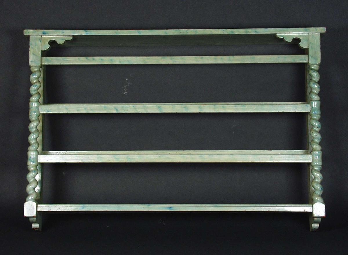 Tallerkenhylle i tre høyder. Den er malt i grønnblå marmorering.