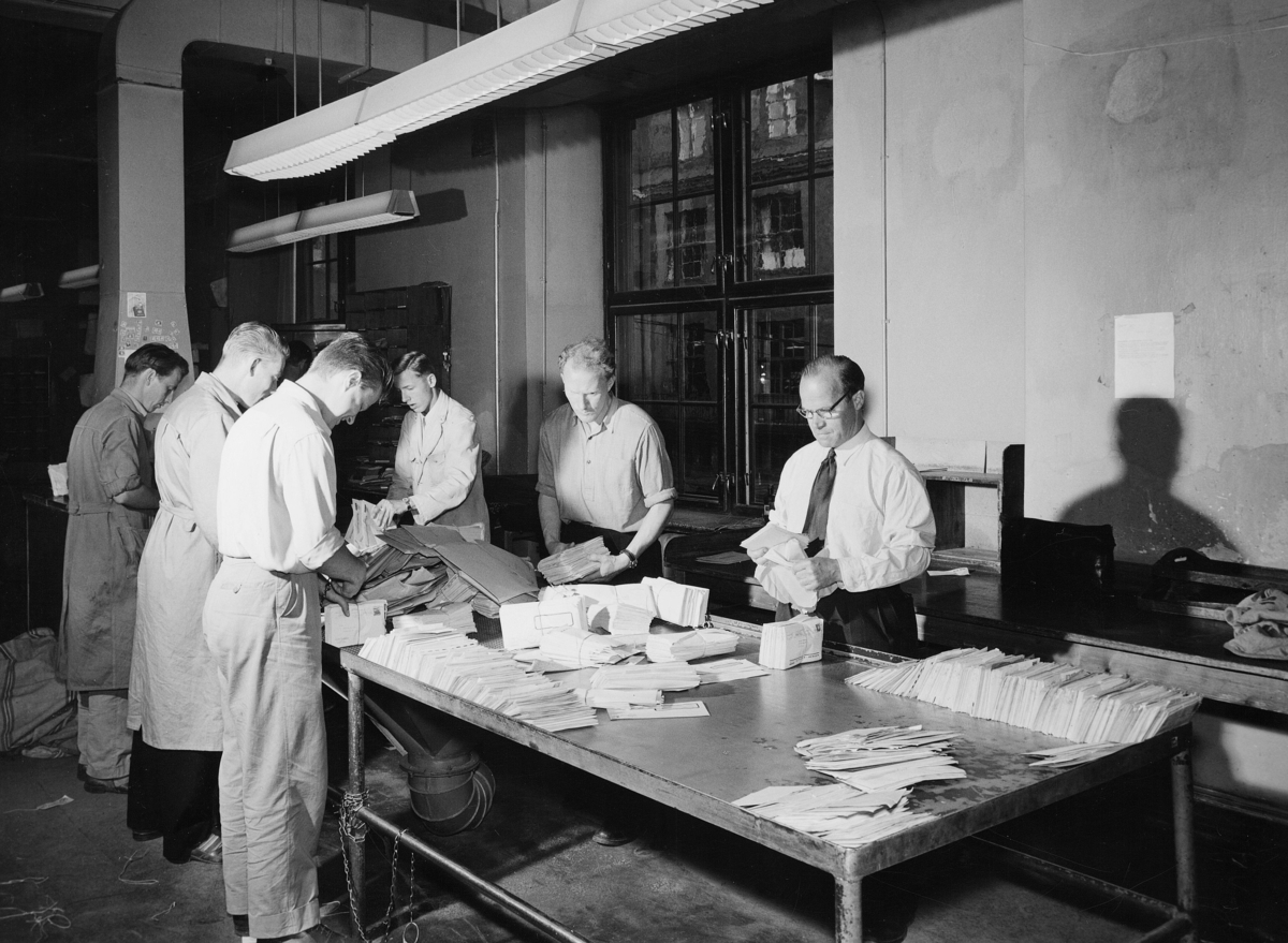 postbehandling, Oslo postgård, Oslo sentrum postkontor, interiør, budavdelingen, åpningsbordet, seks menn står ved et bord og åpner og grovsorterer posten, brev