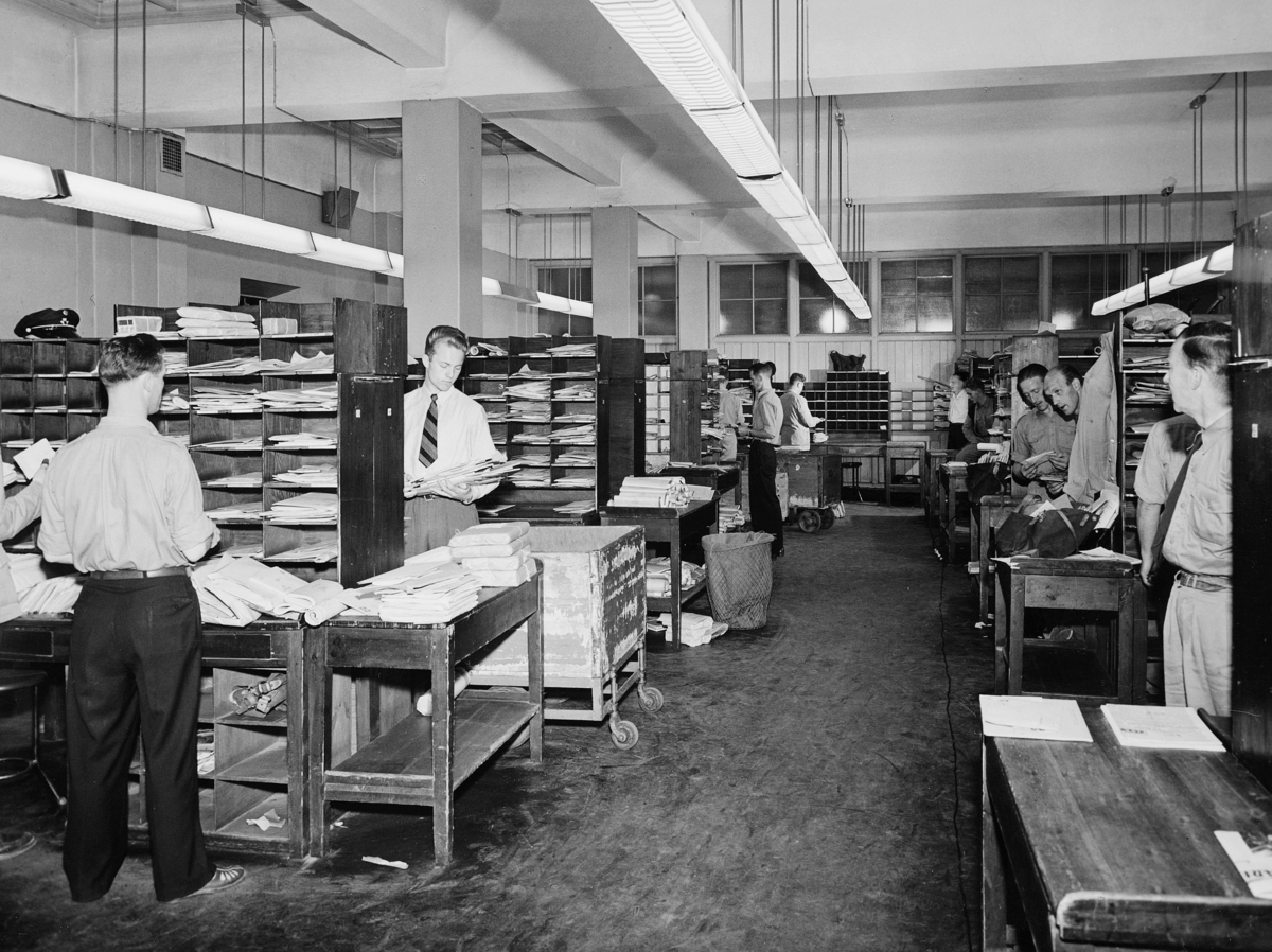 postbehandling, Oslo postgård, Oslo sentrum postkontor, interiør, budavdelingen, sentrum budsal, sortering, sorteringsreoler, posttraller, papirkurv, menn står og sorterer post