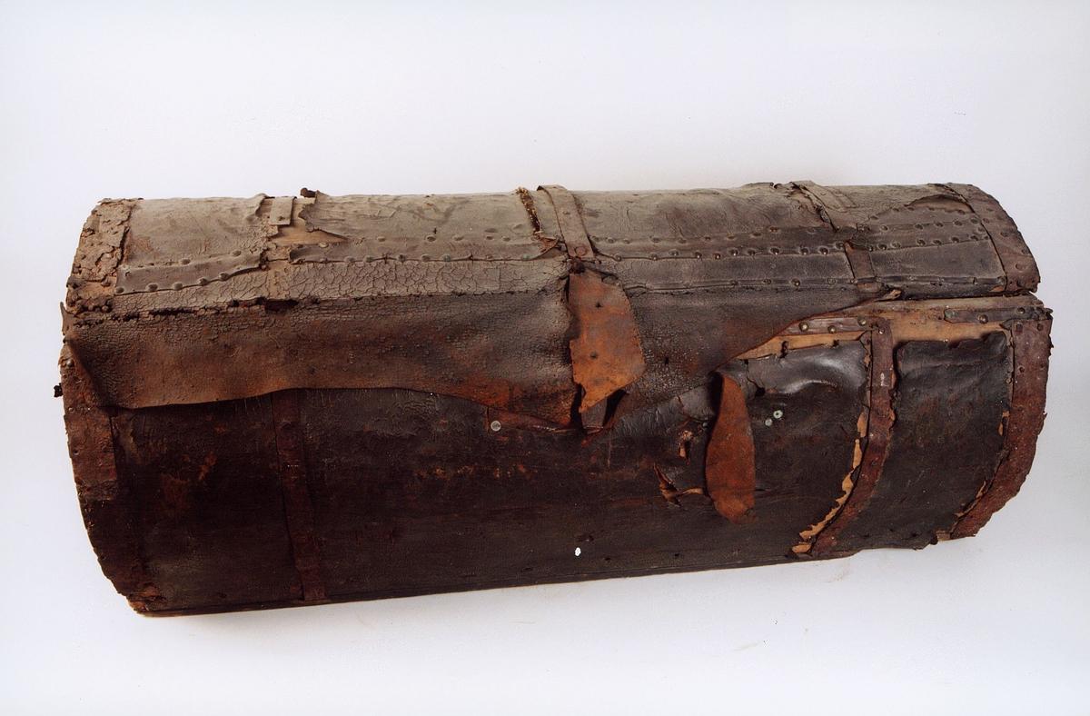 Kjøreveske -for hestevogn, brukt i posttransport med hest og vogn. I tre, trukket med skinn. Veska er rund, og har lokk og håndtak på sidene.