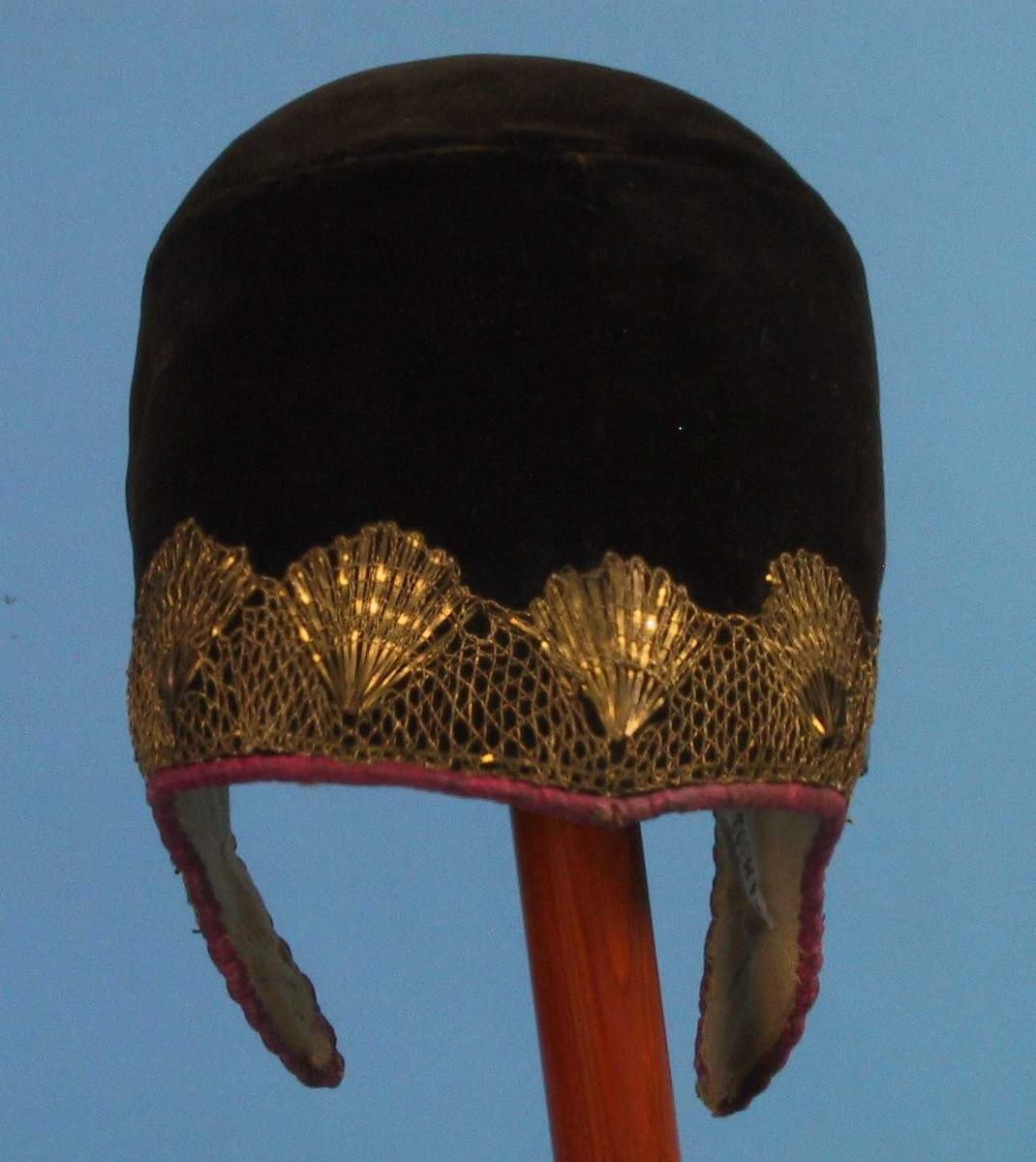 Brudelue. Fløyel, brun, kantet med cyklamenfarvet silke,  fløyelen besatt langs kanten med gullblonde.   Hettefasong med øreklaffer.  Stivt innlegg, for: hvitt lerret.