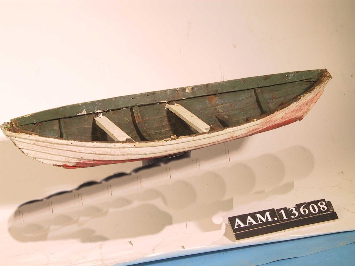 Skjekte, modell/lekebåt. Furu, malt hvit, engelskrød, grønn.    Klinkbygget, utv. hvitmalt  med rød kjøl,  rester av underliggende farger.  Innv. dyp grønn med to hvitmalte tofter. Tilstand: bunn og kjøl borte, likeså esingen  på den ene side.