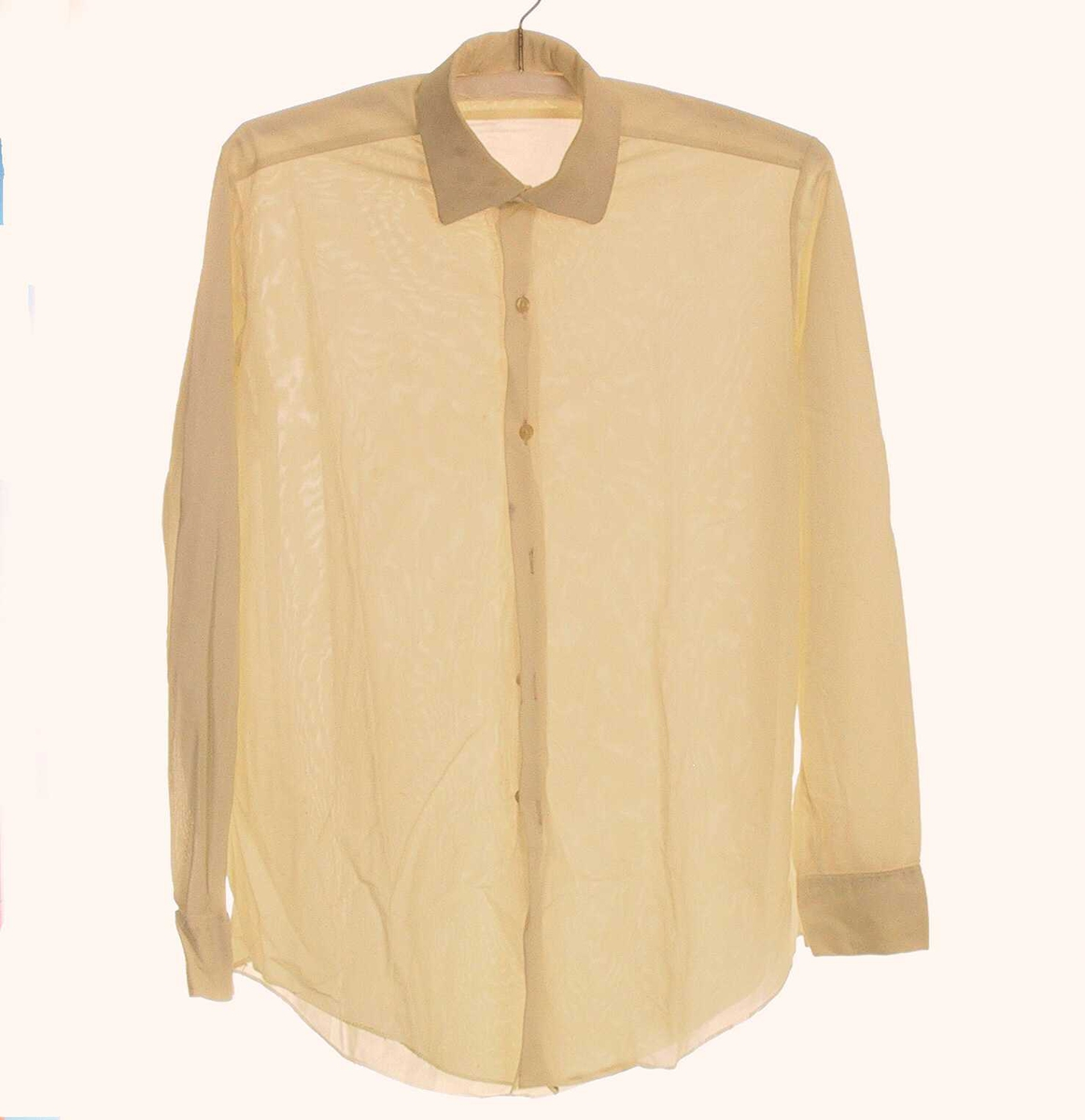 Skjorte med liten nedslagskrave, isatt stykke over skulderparti. Svinget nedrekant, lengst midt foran og midt bak.