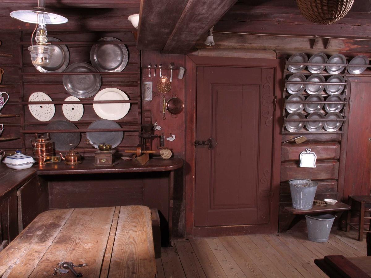 Merdøgaard. Interiør kjøkkenet. Tinntallerkner m.m. i rekker på brunmalt vegg. Kjøkkenbord, skurebøtter.