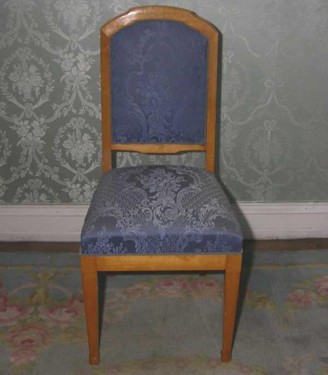 Mellomblå brokademønstret stol med treverk i bjørk. Buet, stoppet rygg, adskilt fra setet.