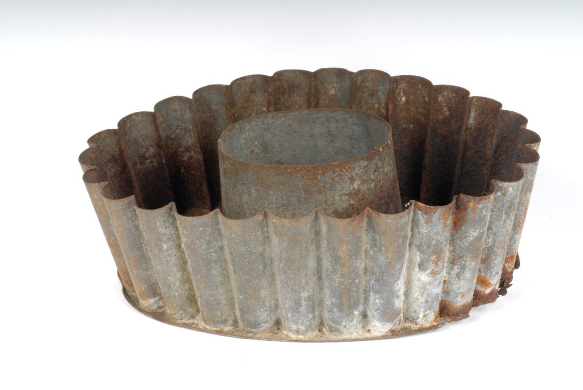 """Form: Oval med bølgede sider Oval oppstander med slett overflate i midten - for å lage hull i puddingen. Tidl. reg.: """"Fiskepuddingformer - Johs. Fløtten"""" Lå sammen med nr. 57"""