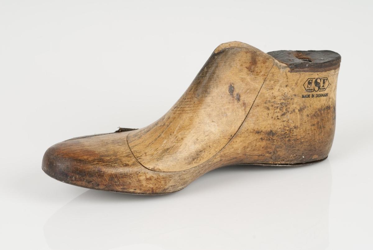 En trelest i to deler; lest og overlest (kile). Høyrefot i skostørrelse 43. Såle av metall. Lestekam av skinn