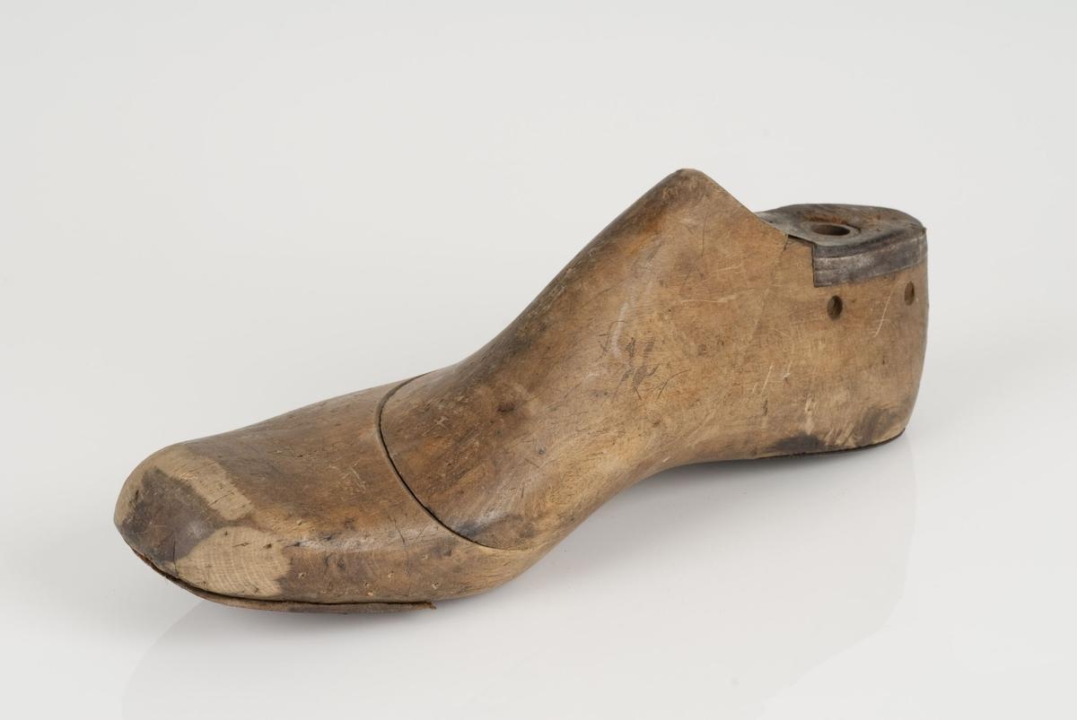 En tremodell i to deler; lest og opplest/overlest (kile). Høyrefot i skostørrelse 44, og 8 cm i vidde. Hælstykket i metall. Lestekam i skinn. Tåspringsåle i skinn.