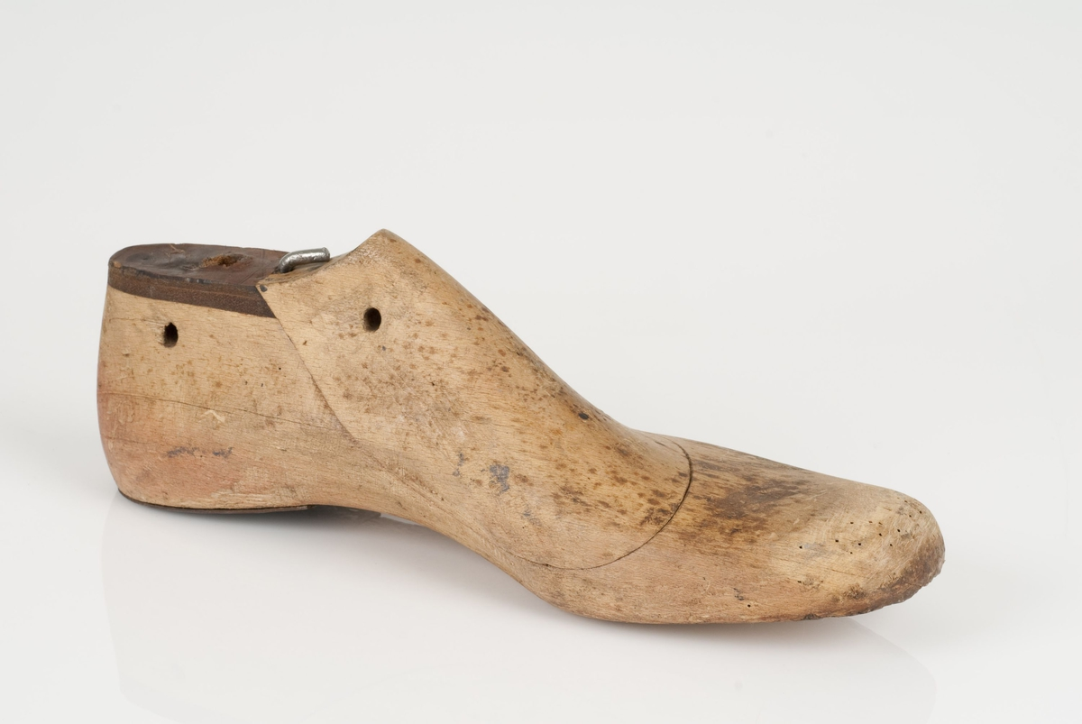 En tremodell i to deler; lest og opplest/overlest (kile). Venstrefot i skostørrelse 46, og 8 cm i vidde. Hælstykket i metall. Lestekam i skinn. Skrue som holder fast kile og lest.
