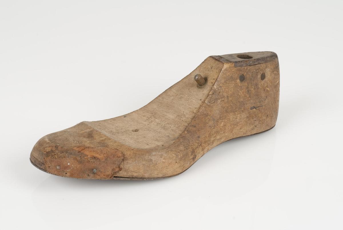 En tremodell; lest (uten overlest). Høyrefot i skostørrelse 34, og 8 cm i vidde. Lestekam av skinn. Såle av metall.