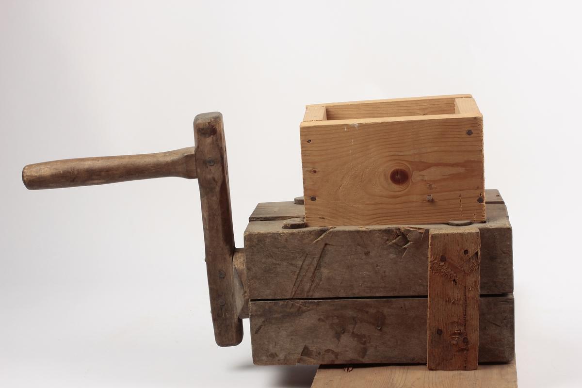 Kvern av tre. Opprinnelig en rektangulær kvern, sammensatt med trenagler. Den er senere festet på et brett og har fått en kasse spikret på over innmatingsåpningen.