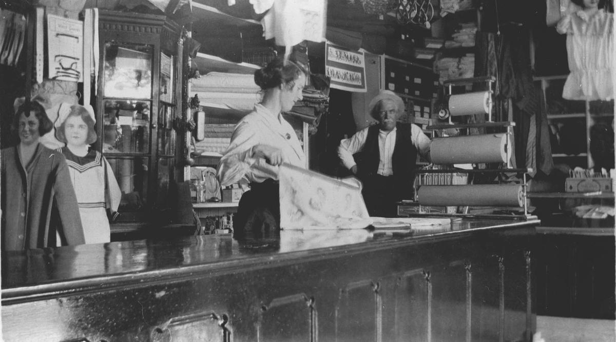 Interiør manufakturbutikk. En kvinne bak disken og Herman Grøn-Hansen i bakgrunnen.